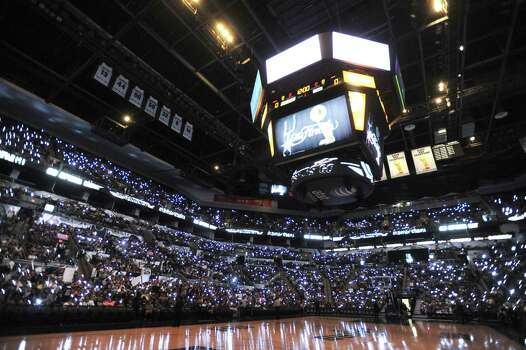 Fans in the AT&T Center shine their flashlights before watching NBA Finals Game 7 between the Spurs and the Miami Heat in Miami on big screen during a viewing party on Thursday night, June 20, 2013. Photo: Billy Calzada, San Antonio Express-News / San Antonio Express-News