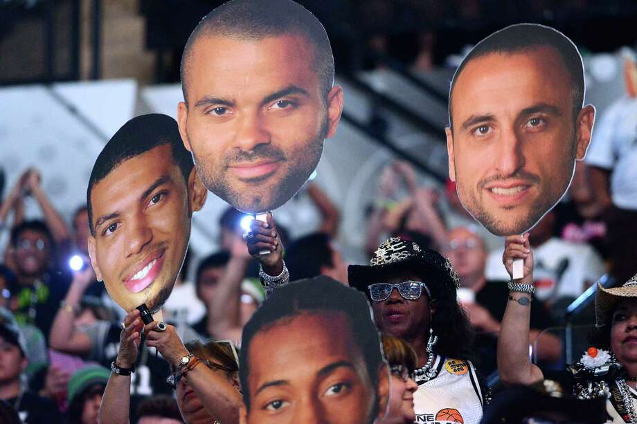 Fans holds up posters of their favorite Spurs as they watch the NBA Finals Game 7 between the Spurs and the Miami Heat in Miami on big screen during a viewing party at the AT&T Center, the  Spurs home court, on Thursday night, June 20, 2013. Th Photo: Billy Calzada, San Antonio Express-News / San Antonio Express-News
