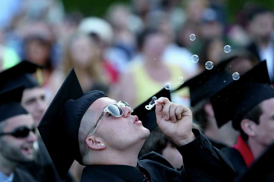 Mike Ross Connecticut Post freelance - Platt Tech graduate Patrick Sheehan of Milford blows bubbles during Thursday afternoon's commencement exercises. Photo: Mike Ross / Mike Ross Connecticut Post freelance -www.mikerossphoto.com