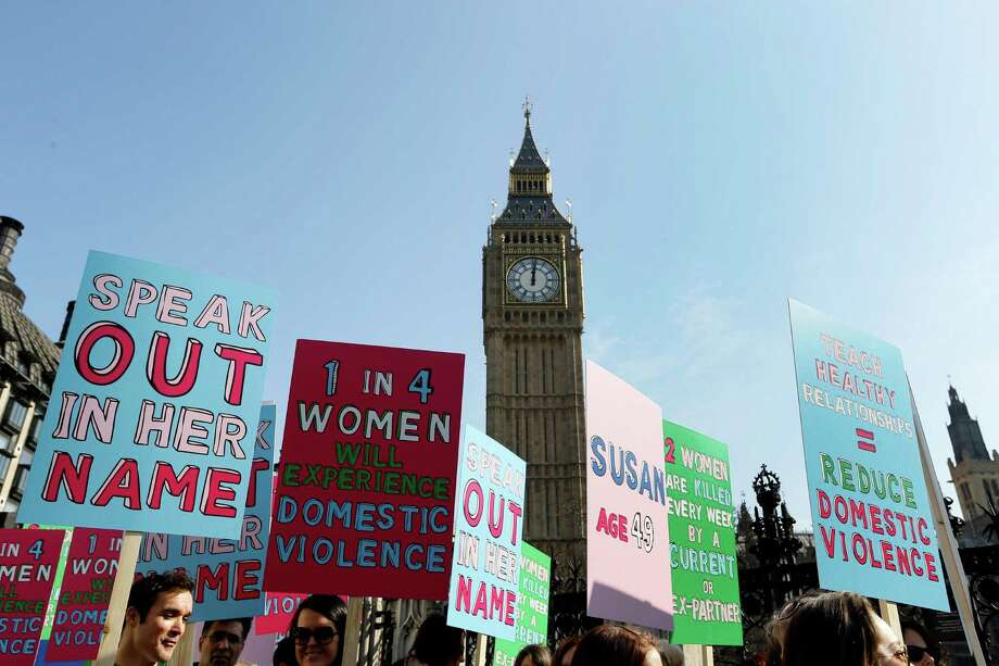 FILE - In this Tuesday, March 5, 2013 file photo people hold banners during a demonstration against domestic violence near Big Ben in London, in the lead up to International Women's Day. About a third of women worldwide have been physically or sexually assaulted by a former or current partner, according to the first major review of violence against women. In a series of papers released on Thursday June 20, 2013 by the World Health Organization and others, experts estimated nearly 40 percent of women killed worldwide were slain by an intimate partner and that being assaulted by a partner was the most common kind of violence experienced by women. (AP Photo/Kirsty Wigglesworth, File) Photo: Kirsty Wigglesworth