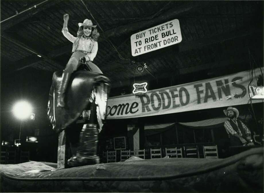 "Lynn Wyatt rides the mechanical bull at Gilley's Club during a party celebrating the opening of ""Urban Cowboy"" in May 1980. Photo: Fred Bunch, HP Staff"