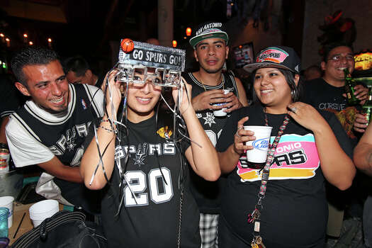 Helen Roadriguez tries on her lighted glasses as Spurs fans watch game 7 of the NBA finals at Moses Rose's Tavern  San Antonio .   Behind from left are Daniel Loera Joe Weddel, Jr. and Evelyn Elizondo. June 20, 2013. Photo: Tom Reel, San Antonio Express-News