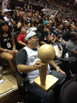 One fan sits intently watching the big screen at the AT&T Center Thursday night, clutching a homemade championship trophy. Photo: Michelle Casady / San Antonio Express-News