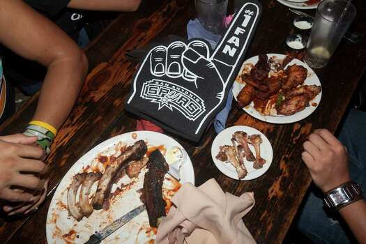 A foam finger sits beside some ribs and wings at County Line Barbecue in San Antonio on Thursday, June 20, 2013. Photo: Abbey Oldham, San Antonio Express-News / © San Antonio Express-News