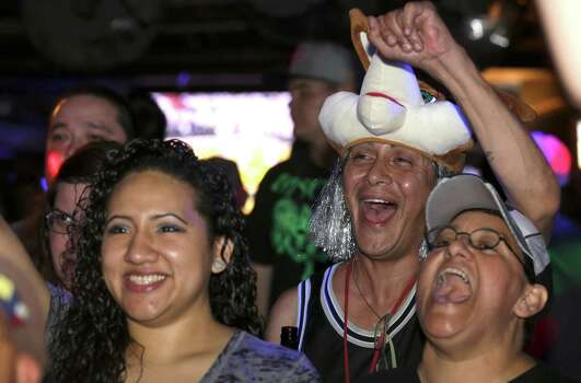 San Antonio Spurs fans Valerie Morales, left to right, Ronnie Morin, and Cris Campos celebrate a Spurs score in the first half as they watch the game at the Basement Bar nd Lounge on Thursday, June, 20, 2013. Photo: Bob Owen, San Antonio Express-News / ©2013 San Antonio Express-News