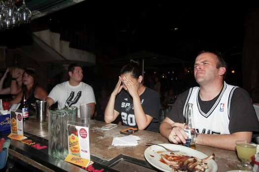 Fans, right to left, Zach Warren, Victoria Bazaldua, and Abel Esparaza, all of San Antonio, sit at the bar at Barriba Cantina in downtown San Antonio to watch the Spurs play in the NBA Finals on Thursday, June 20, 2013. Photo: Abbey Oldham, San Antonio Express-News / © San Antonio Express-News