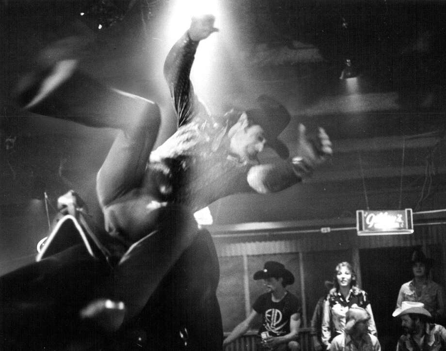"Gilley's (Nightclub); Travolta Rode Here: Urban Cowboy Gets Thrown From El Toro, The Mechanical Bull In Gilley's Club Near Houston; ""Risking your manhood in order to prove it,"" in a macho-man oasis surrounded by oil-refinery surrealism. Photo: Joe Sinisi, Denver Post Via Getty Images / Denver Post"