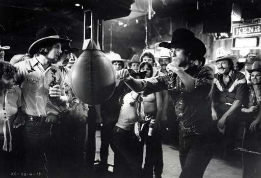 "A cowboy in a modern setting, John Travolta applies his force to the new punching bag installed at Gilley's, the largest honky-tonk in America, in ""Urban Cowboy."" Photo: Paramount Pictures / handout"