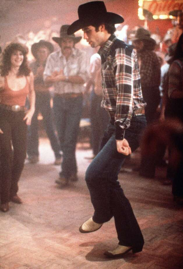 John Travolta as Bud in the 1979 film Urban Cowboy dances as co-star Debra Winger, far left, looks on. A stage version of the film debuts this week in Miami with newcomer Michael Cavenaugh in the role made famous by Travolta. Photo: AP / FILE