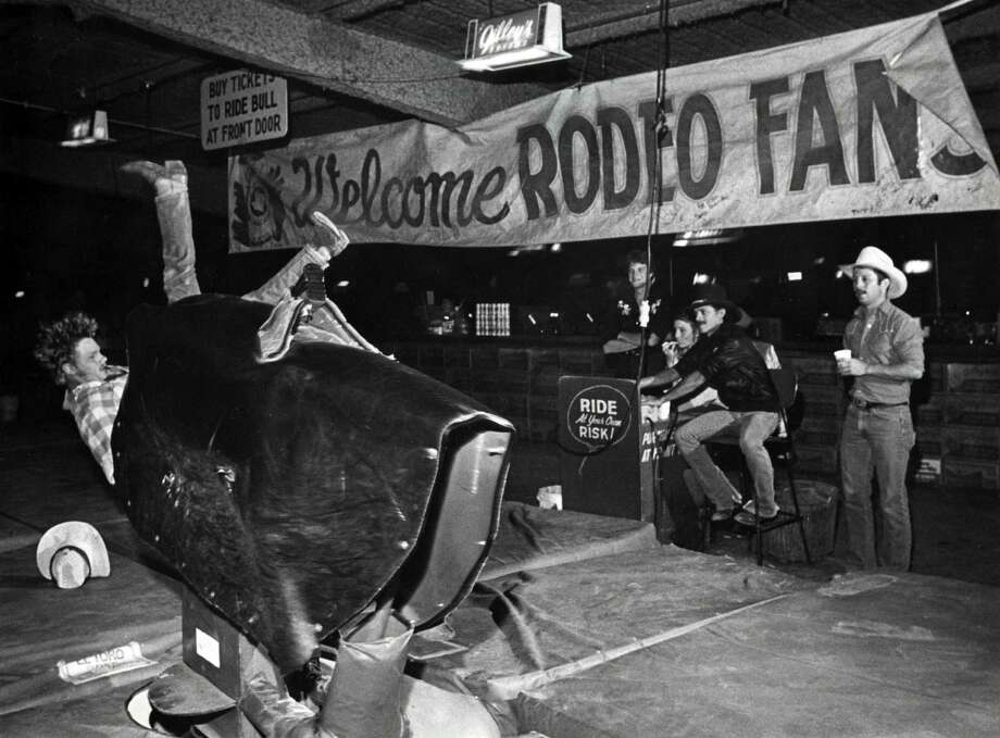 Lance Turner falls off the mechanical bull at Gilley's Club. Photo: Ben DeSoto, Houston Chronicle / Houston Chronicle