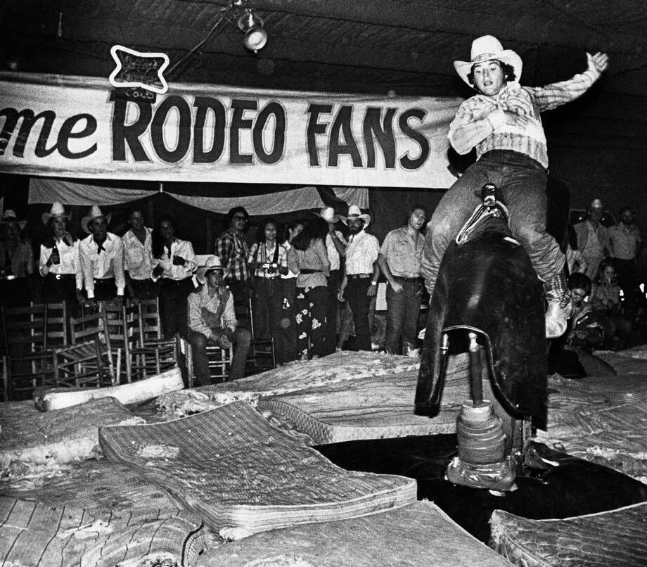 A patron of Gilley's Club, flings his arm back as he rides the mechanical bull at the popular country and western night club outside of Houston on Dec.17,1980. Photo: Anonymous, ASSOCIATED PRESS / AP1980