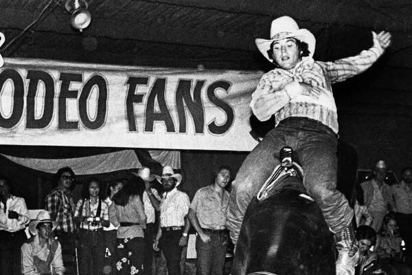 A patron of Gilley's Club, flings his arm back as he rides the mechanical bull at the popular country and western night club outside of Houston on Dec.17,1980.