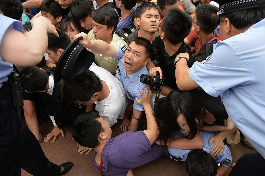 "People fall in a stampede to see football superstar David Beckham at Tonji University in Shanghai on June 20, 2013. Beckham's visit to China turned ""chaotic"" on June 20 after at least five people were hurt in a stampede as fans rushed to see him, local media and an AFP photographer at the scene said.