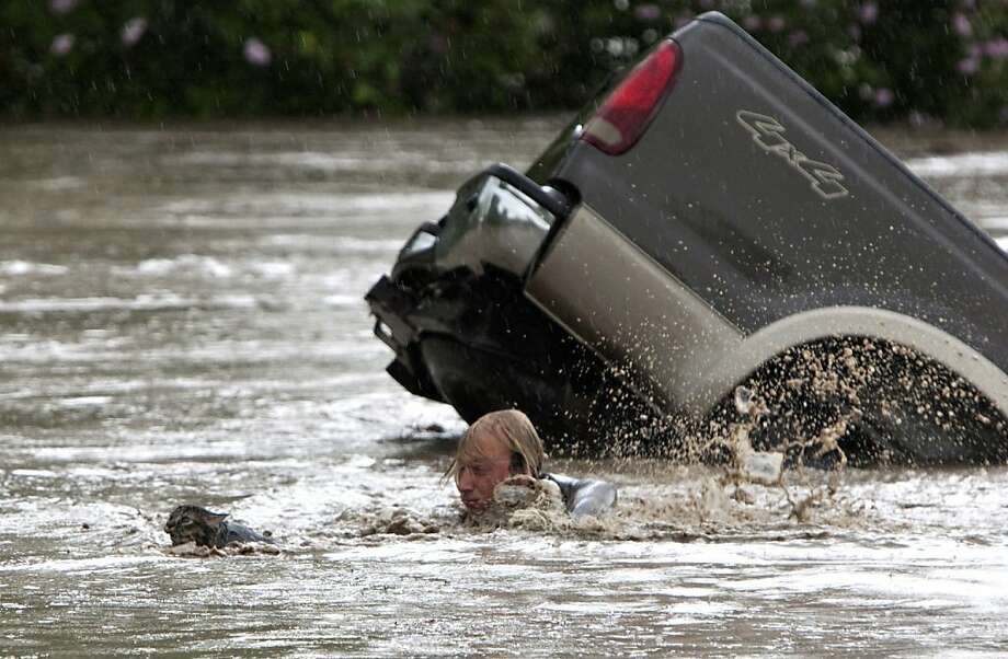 Four-wheel fail: Kevan Yaets swims after his cat, Momo, after high water swamped his truck in High River, Alberta. Fortunately, both Yaets and Momo managed to reach shore safely with a little help from two men who jumped in the water to assist them. Photo: Jordan Verlage, Associated Press