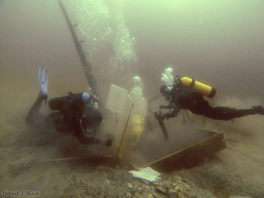 Divers inspect a hole being dug beside a wooden beam jutting from the floor of Lake Michigan that an exploration group believes may have been part of the 17th-century ship the Griffin.