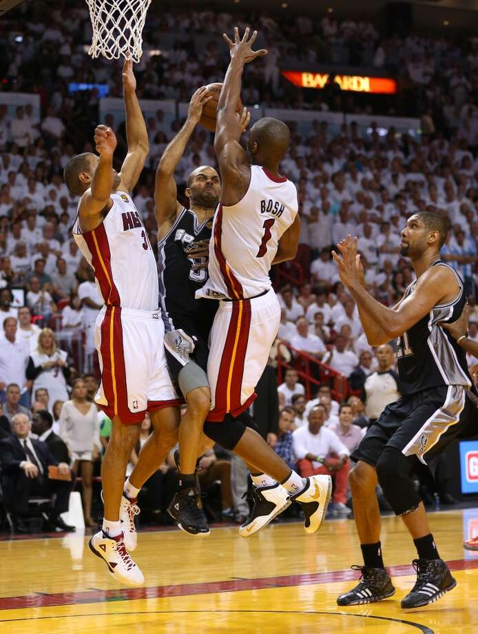 Tony Parker of the Spurs drives on Shane Battier #31 and Chris Bosh #1 in the fourth quarter. Photo: Mike Ehrmann, Getty Images