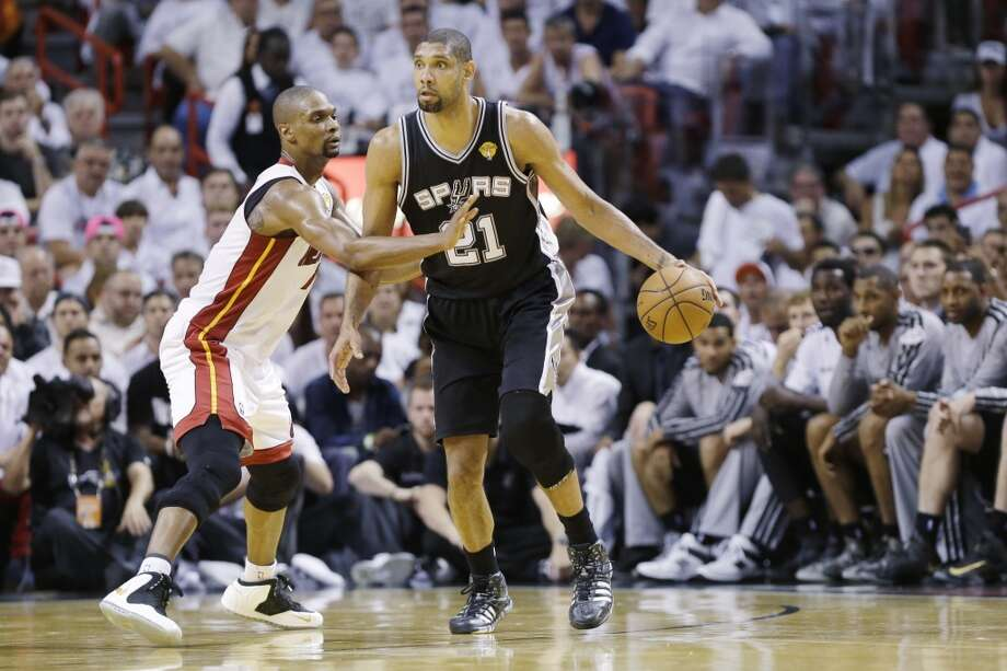 Tim Duncan is defended by Chris Bosh. Photo: Lynne Sladky, Associated Press