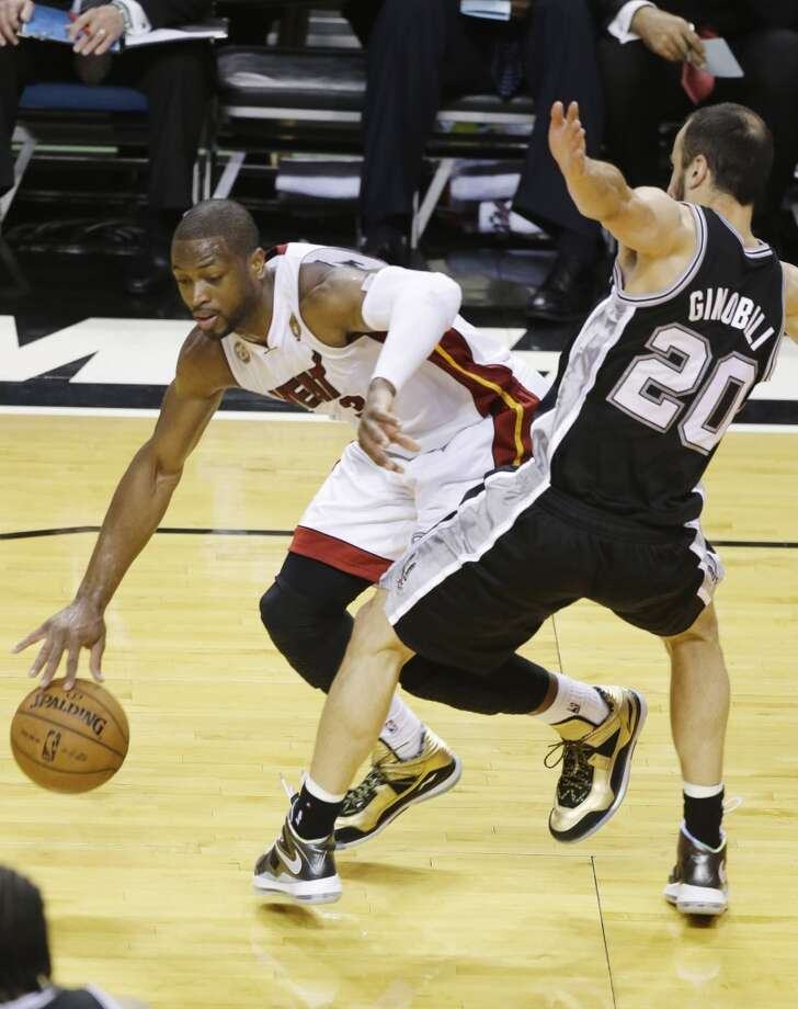 Dwyane Wade drives around Manu Ginobili. Photo: Wilfredo Lee, Associated Press