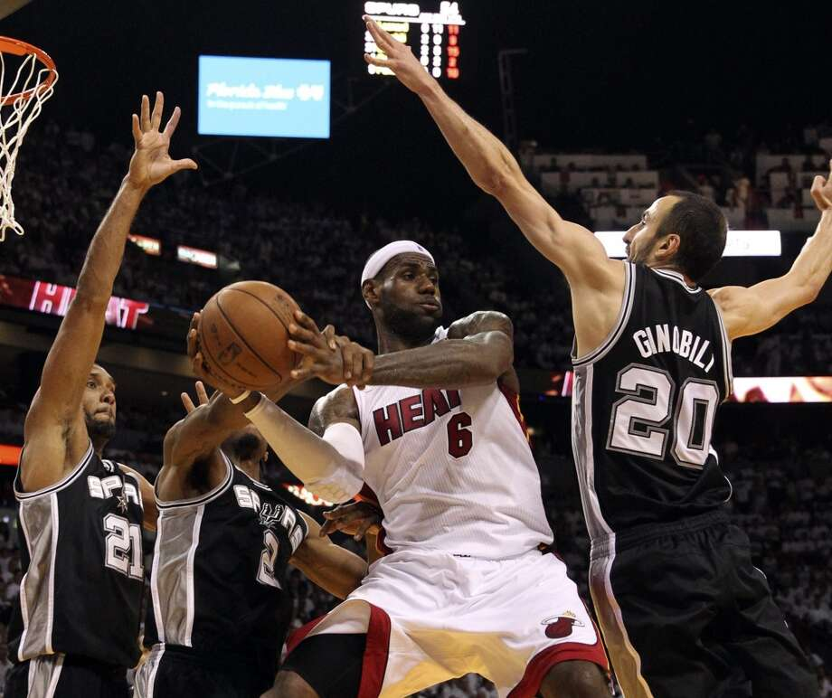 LeBron James passes the ball while surrounded by Spurs defenders. Photo: CHARLES TRAINOR JR., McClatchy-Tribune News Service