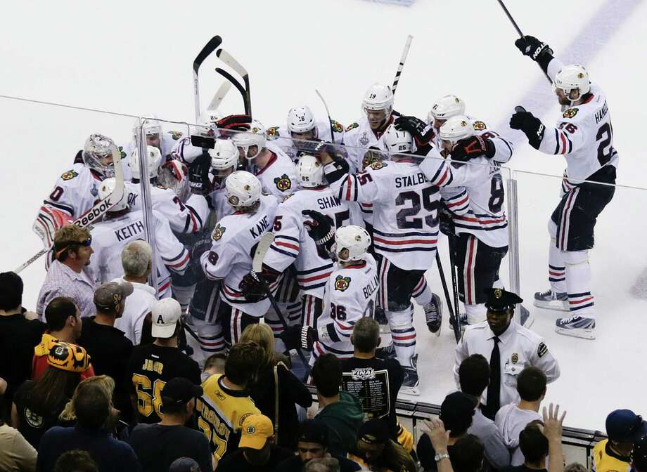 The Chicago Blackhawks mob Brent Seabrook, after his game-winning goal against the Boston Bruins during the first overtime period in Game 4 of the NHL hockey Stanley Cup Finals, Wednesday, June 19, 2013, in Boston. Chicago won 6-5. (AP Photo/Charles Krupa) Photo: Charles Krupa