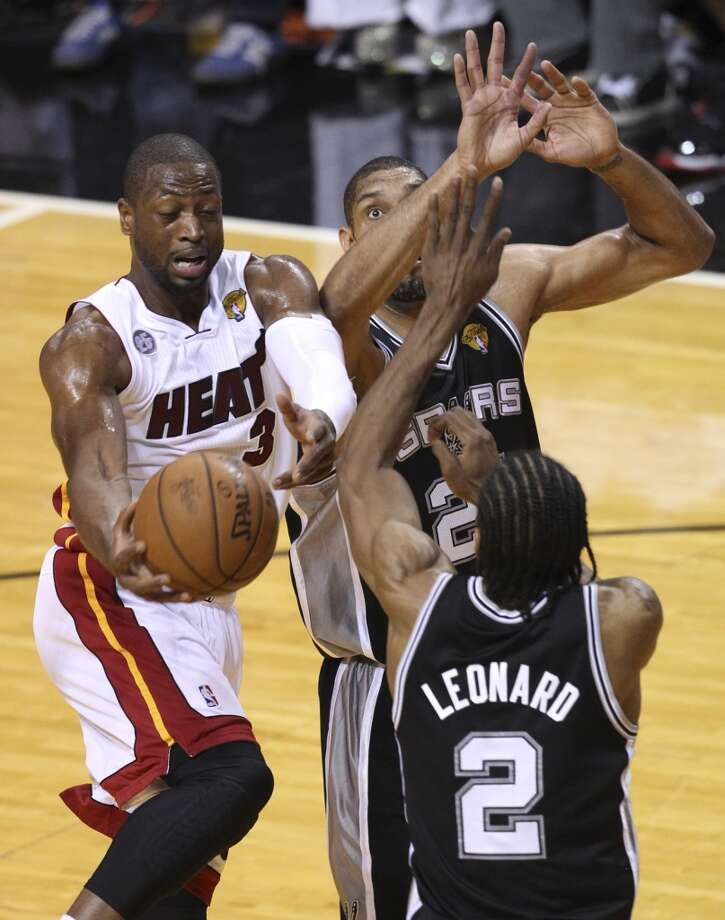 Miami Heat's Dwyane Wade tries to dish out of the paint while under pressure from San Antonio Spurs' Tim Duncan and Kawhi Leonard during the first half of Game 7 of the NBA Finals at American Airlines Arena on Thursday, June 20, 2013 in Miami. (Kin Man HuiSan Antonio Express-News) Photo: Kin Man Hui, San Antonio Express-News