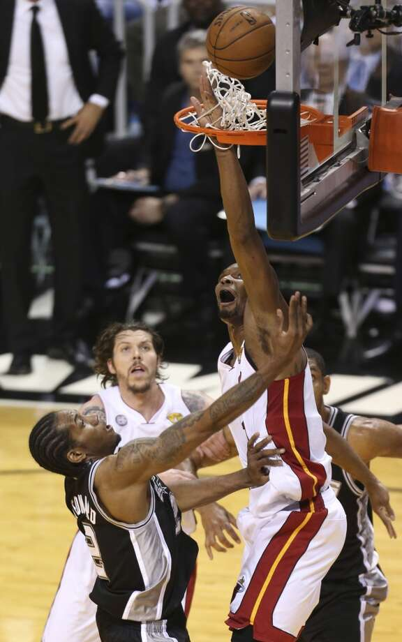 Miami Heat's Chris Bosh gets his hand in the net while trying to defend San Antonio Spurs' Kawhi Leonard during the first half of Game 7 of the NBA Finals at American Airlines Arena on Thursday, June 20, 2013 in Miami. (Jerry Lara/San Antonio Express-News) Photo: Jerry Lara, San Antonio Express-News
