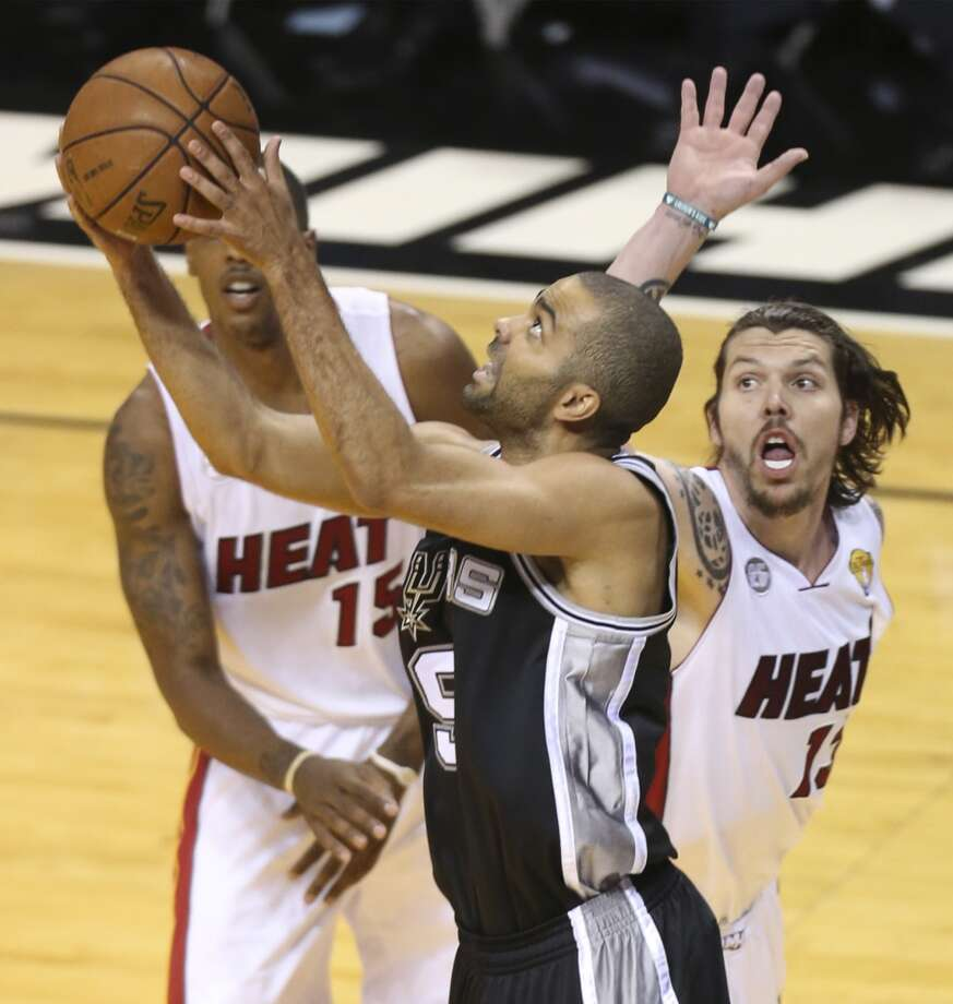 San Antonio Spurs' Tony Parker shoots from under the net while being defended by Miami Heat's Mario Chalmers and Mike Miller during the first half of Game 7 of the NBA Finals at American Airlines Arena on Thursday, June 20, 2013 in Miami. (Jerry Lara/San Antonio Express-News) Photo: Jerry Lara, San Antonio Express-News