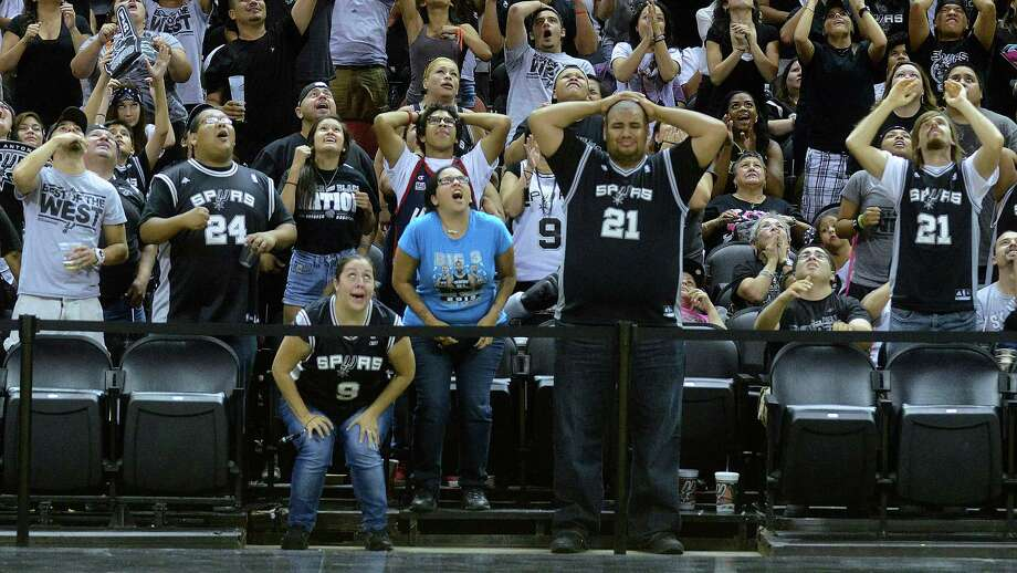 In middle front, Kimberly Singer, left, Leeza Morales and Manuel Lopez react as time winds down on the Spurs loss to the Miami Heat in the NBA Finals Game 7. They watched the game on a big screen at the AT&T Center, the  Spurs home court, on Thursday night, June 20, 2013. Photo: Billy Calzada, San Antonio Express-News / San Antonio Express-News