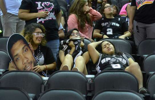 Caitlyn Sada, left, Michelle Paredes and Sabrina Paredes are saddened by the Spurs loss to the Miami Heat in the NBA Finals Game 7. They watched the game on a big screen at the AT&T Center, the  Spurs home court, on Thursday night, June 20, 2013. Photo: Billy Calzada, San Antonio Express-News / San Antonio Express-News