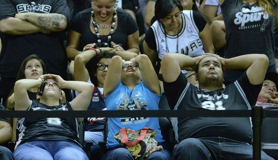 Kimberly Singer, left, Leeza Morales and Manuel Lopez react as time winds down on the Spurs loss to the Miami Heat in the NBA Finals Game 7. They watched the game on a big screen at the AT&T Center, the  Spurs home court, on Thursday night, June 20, 2013. Photo: Billy Calzada, San Antonio Express-News / San Antonio Express-News