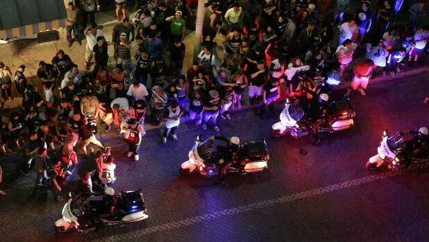 SAPD push the crowd back as fans take to the streets downtown after the Spurs lost to the  Miami Heat in game 7 for the NBA Championship on Thursday, June, 20, 2013. Photo: Bob Owen, San Antonio Express-News / ©2013 San Antonio Express-News