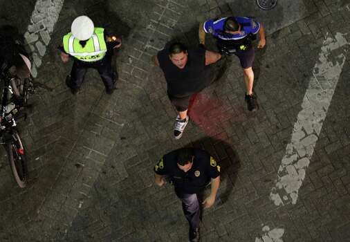 A man is arrested by SAPD as Spurs fans take to the streets downtown after the Spurs lost to the  Miami Heat in game 7 for the NBA Championship on Thursday, June, 20, 2013. Photo: Bob Owen, San Antonio Express-News / ©2013 San Antonio Express-News