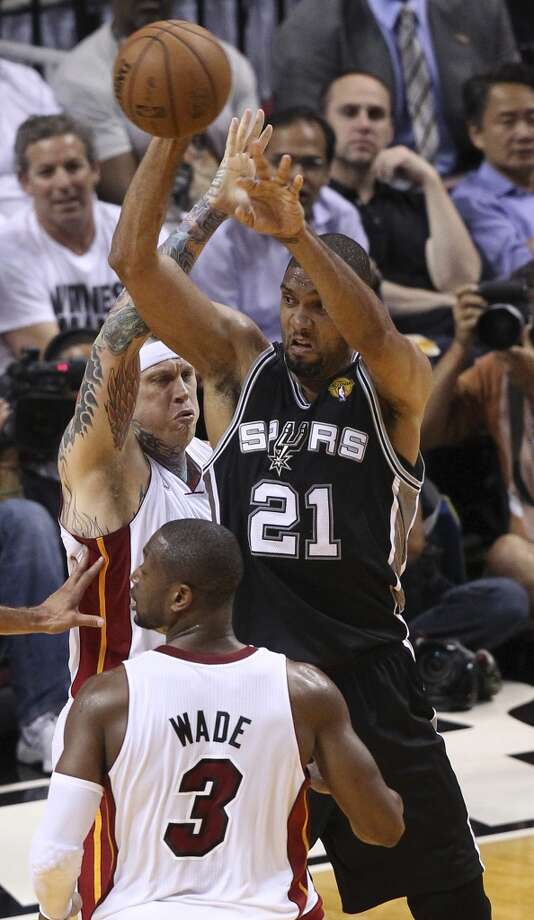 San Antonio Spurs' Tim Duncan passes the ball while under pressure from Miami Heat's Chris Andersen and Dwyane Wade during the first half of Game 7 of the NBA Finals at American Airlines Arena on Thursday, June 20, 2013 in Miami. (Kin Man Hui/San Antonio Express-News) Photo: San Antonio Express-News