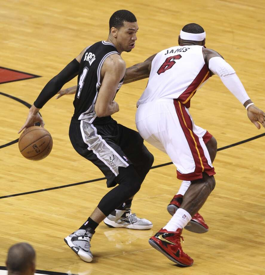San Antonio Spurs' Danny Green does a behind-the=back move as Miami Heat's LeBron James reaches for the ball during the second half of Game 7 of the NBA Finals at American Airlines Arena on Thursday, June 20, 2013 in Miami. (Kin Man HuiSan Antonio Express-News) Photo: San Antonio Express-News