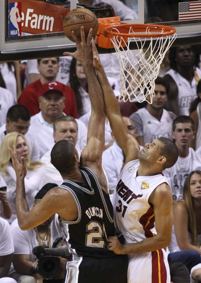 Miami Heat's Chris Bosh grabs San Antonio Spurs' Tim Duncan jersey as Duncan goes for a shot during the first half of Game 7 of the NBA Finals at American Airlines Arena on Thursday, June 20, 2013 in Miami. (Kin Man HuiSan Antonio Express-News) Photo: San Antonio Express-News