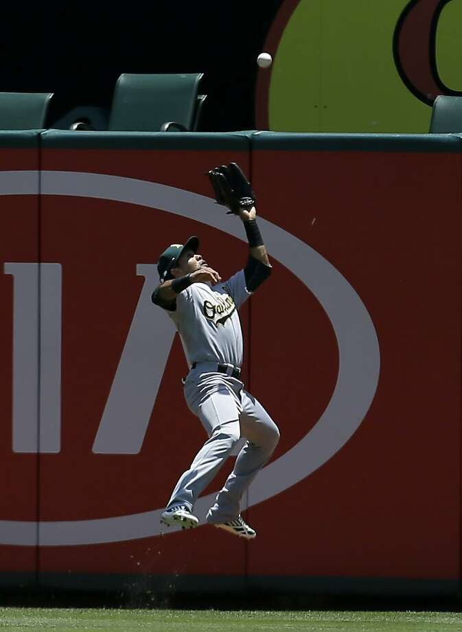 Oakland Athletics center fielder Coco Crisp (4) leaps running back to the wall to grab a fly out by Texas Rangers' Robinson Chirinos in the second inning of a baseball game Thursday, June 20, 2013, in Arlington, Texas. (AP Photo/Tony Gutierrez) Photo: Tony Gutierrez, Associated Press