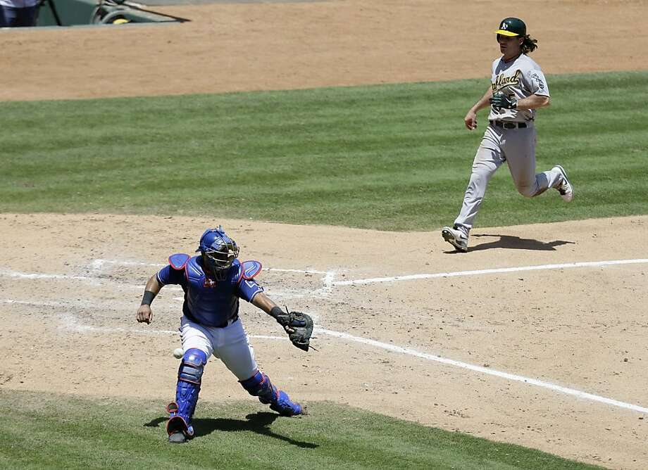 Texas Rangers catcher Geovany Soto reaches out for the throw as Oakland Athletics' John Jaso (5) scores on a Jed Lowrie single in the fifth inning of a baseball game Thursday, June 20, 2013, in Arlington, Texas. (AP Photo/Tony Gutierrez) Photo: Tony Gutierrez, Associated Press