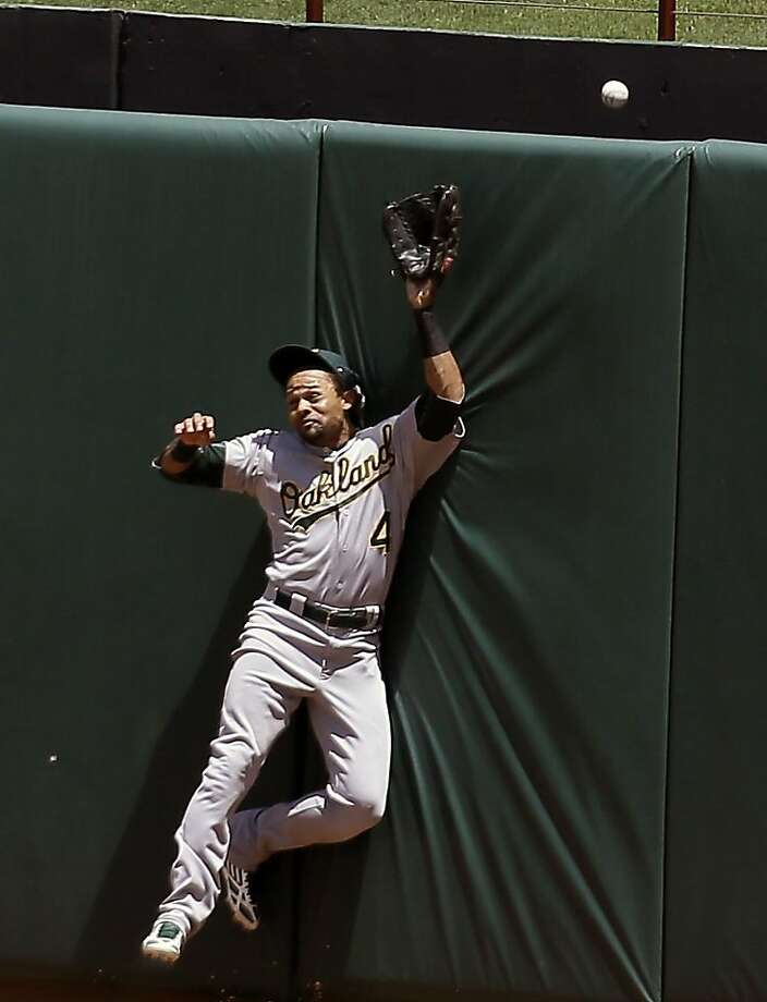 Oakland Athletics' Coco Crisp (4) slams against the centerfield wall while chasing a solo home run by Texas Rangers' Geovany Soto in the fifth inning of a baseball game on Thursday, June 20, 2013, in Arlington, Texas. (AP Photo/Tony Gutierrez) Photo: Tony Gutierrez, Associated Press
