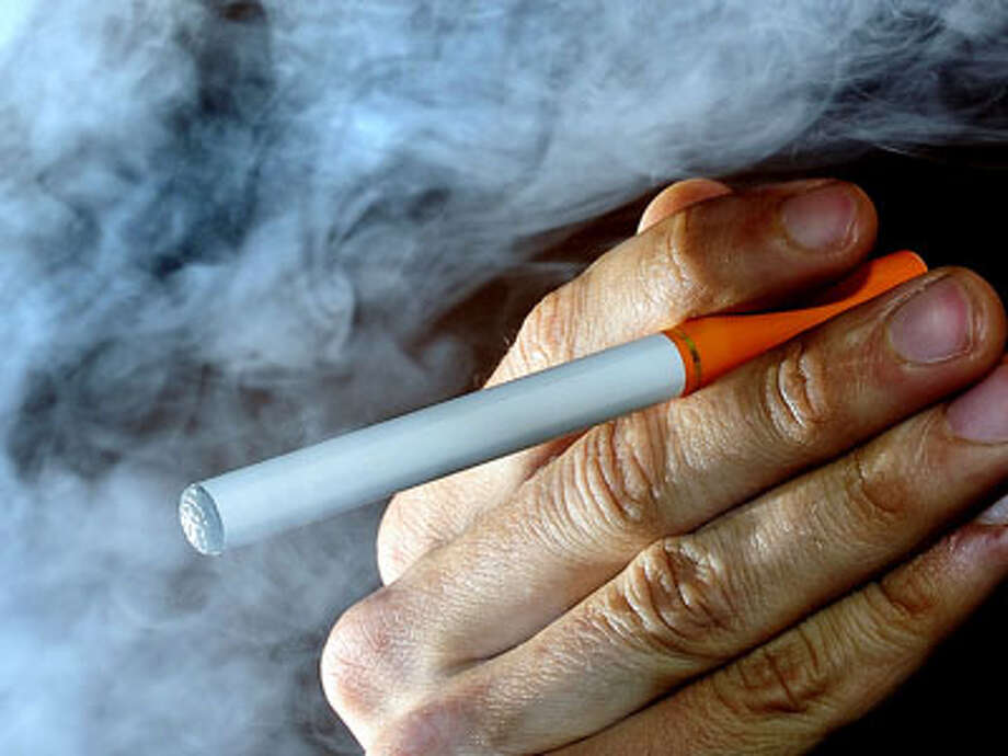 A person poses with an electronic cigarette, or e-cigarette, Wednesday June 12, 2013, after it was announced that Britain will start regulating electronic cigarettes as medicines, according to the country's top regulator, the Medicines and Healthcare Products Regulatory Agency.  E-cigarettes are battery-operated products that turn nicotine into a vapor that is inhaled by the user, and the new regulations coming into force from 2016 will control products containing nicotine as medications, but normal cigarettes are exempt from the regulation. (AP Photo / Tim Ireland, PA) UNITED KINGDOM OUT - NO SALES - NO ARCHIVES Photo: Tim Ireland, AP / PA