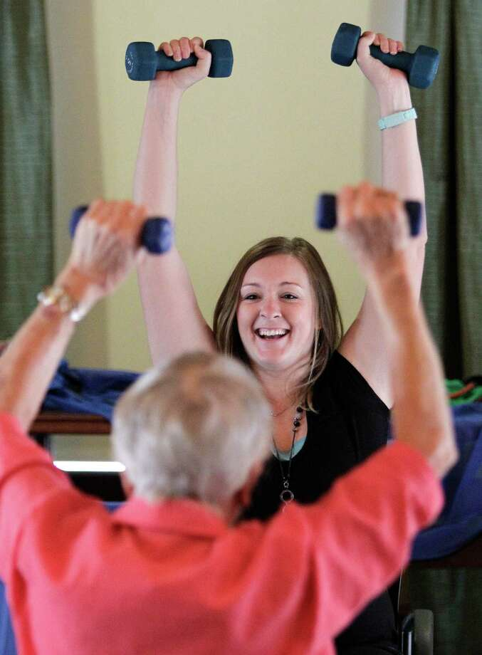 Lavonne Crim, foreground, follows as physical therapist Danielle Ratcliff leads a class at the Village at Gleannloch Farms in Spring. Photo: Melissa Phillip, Staff / © 2013  Houston Chronicle