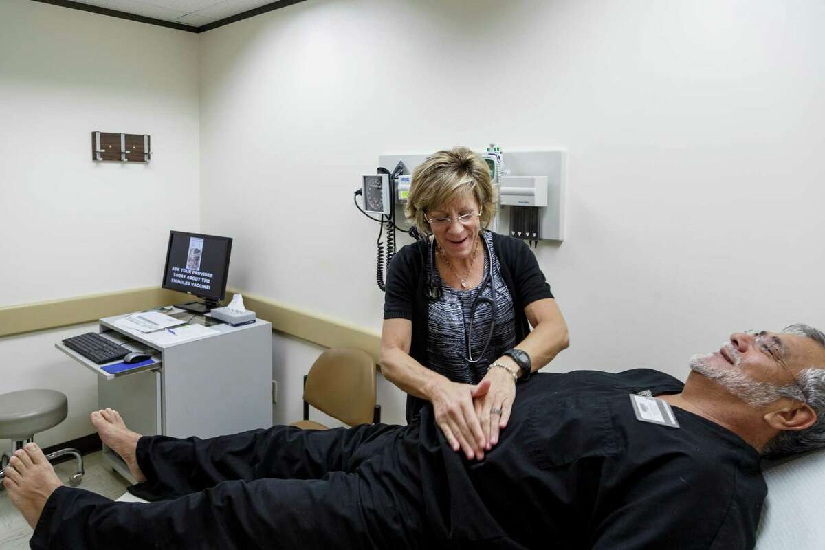 Nurse practitioner Laura Rooney examines Roel Martinez at the health services clinic.