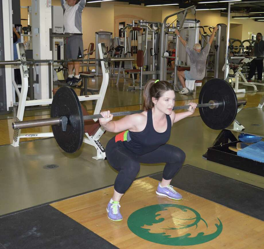 Cherie Troxell, a personal trainer at The Houstonian Hotel, Club and Spa, demonstrates a squat using weights. Photo: The Houstonian