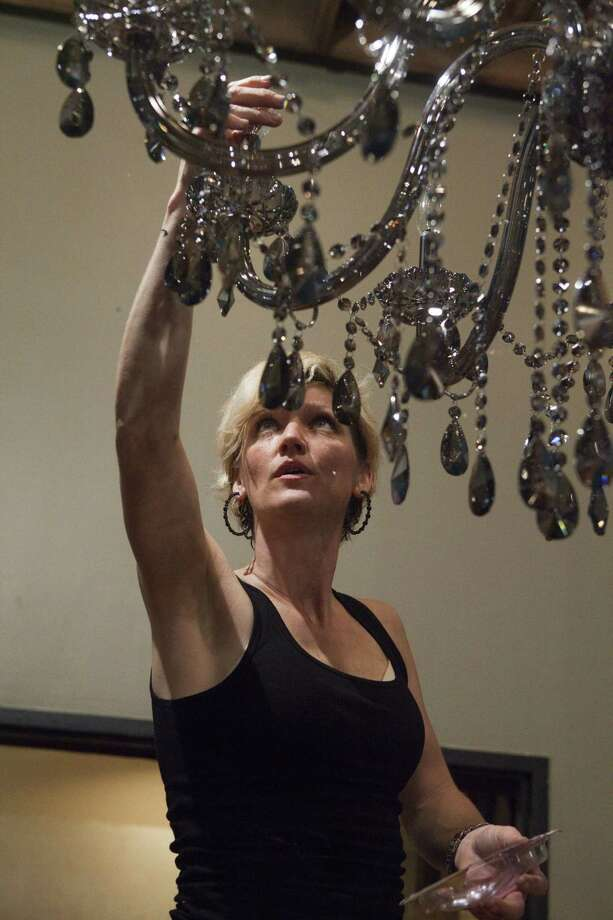 "Abby Vasek puts lightbulbs in a chandelier for ""HGTV Star."" Photo: HGTV"