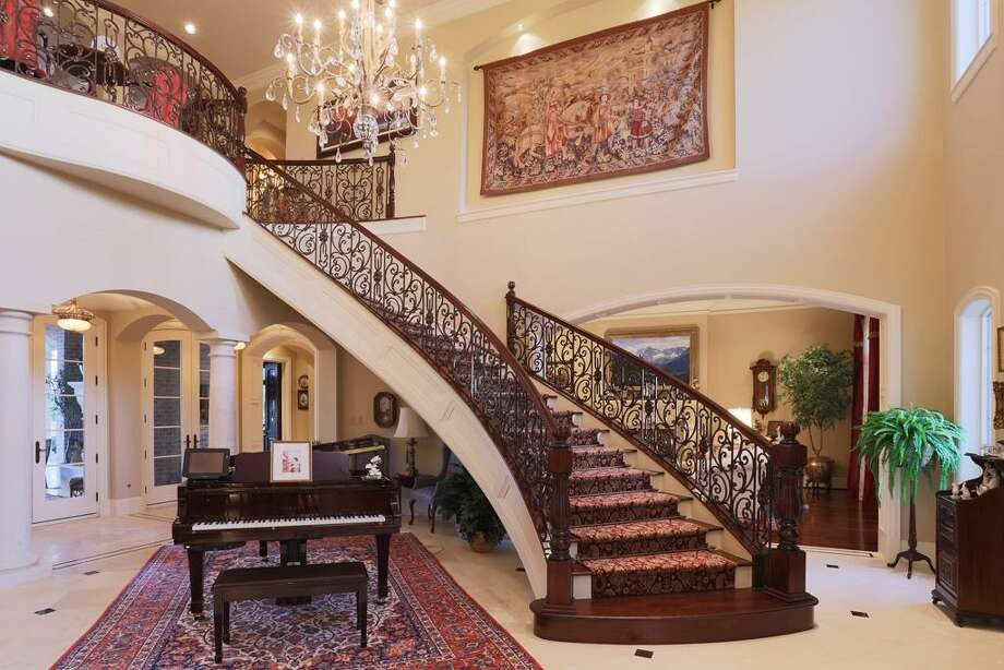 Grand 2 story Foyer measures 24x20 with Travertine flooring. Ample room for a Grand piano under the floating stairway. Note the art niche.