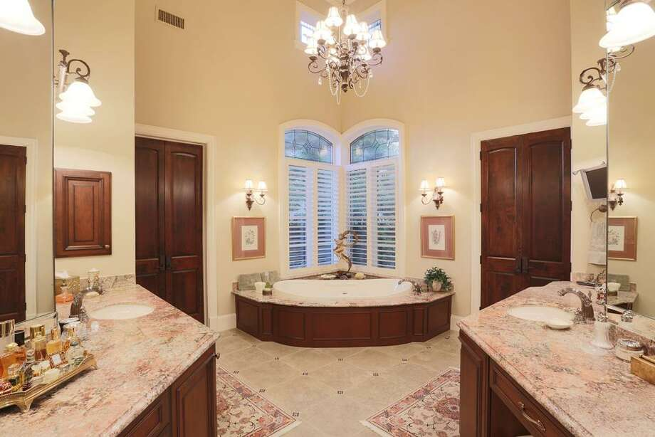 The exotic Granite in this master bath is truly magnificent! The leaded glass transom windows really stand out. There are 2 spacious customized walk in closets. There is also a beverage cooler here.