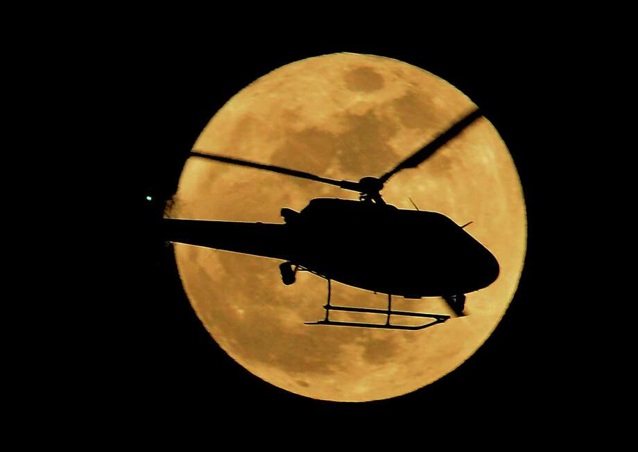 LAPD chopper flies in front of the supermoon in Los Angeles on May 5, 2012. Astronomers say we should expected another supermoon Sunday. (JOE KLAMAR/AFP/GettyImages.) Photo: JOE KLAMAR, Getty/ap / 2012 AFP