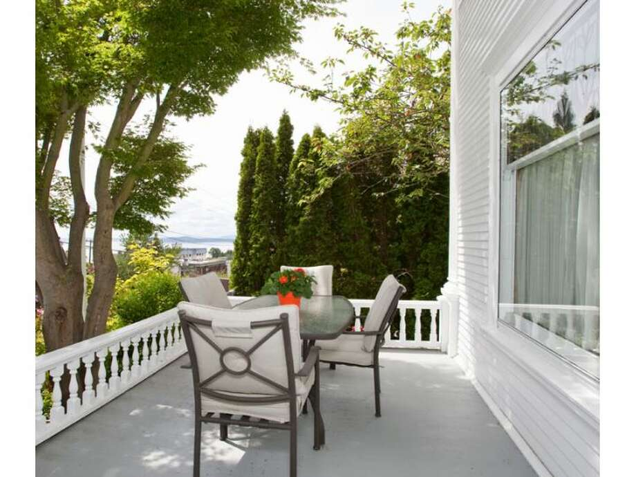 Porch of 120 Prospect St., in Queen Anne. The 5,890-square-foot Georgian Colonial, built in 1904, has six bedrooms, four  bathrooms, a big foyer, birch millwork, leaded glass, a den, a sun porch, a White House-like balcony, a roof deck, a carriage house, a greenhouse, a trout pond with a waterfall, and views of downtown Seattle, Mount Rainier, Elliott Bay and Puget Sound on a 10,200-square-foot lot. It's listed for $1.695 million. Photo: Courtesy Mark Dagg, Windermere Real Estate