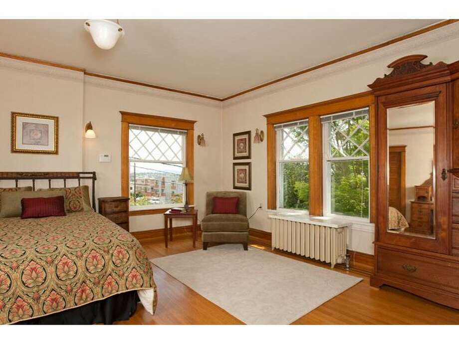 Master bedroom of 120 Prospect St., in Queen Anne. The 5,890-square-foot Georgian Colonial, built in 1904, has six bedrooms, four  bathrooms, a big foyer, birch millwork, leaded glass, a den, a sun porch, a White House-like balcony, a roof deck, a carriage house, a greenhouse, a trout pond with a waterfall, and views of downtown Seattle, Mount Rainier, Elliott Bay and Puget Sound on a 10,200-square-foot lot. It's listed for $1.695 million. Photo: Courtesy Mark Dagg, Windermere Real Estate