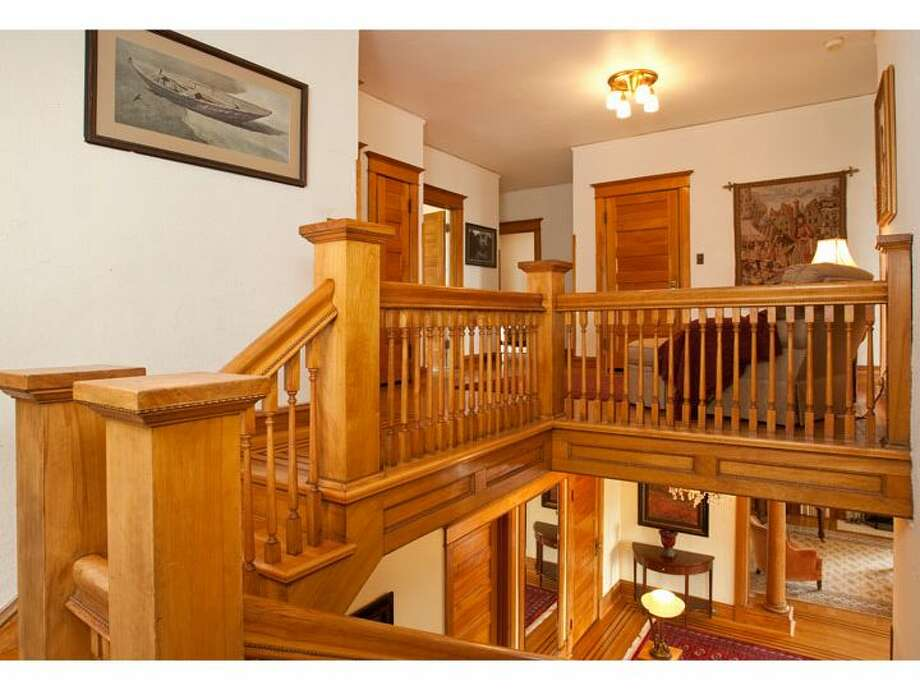 Staircase and landing of 120 Prospect St., in Queen Anne. The 5,890-square-foot Georgian Colonial, built in 1904, has six bedrooms, four  bathrooms, a big foyer, birch millwork, leaded glass, a den, a sun porch, a White House-like balcony, a roof deck, a carriage house, a greenhouse, a trout pond with a waterfall, and views of downtown Seattle, Mount Rainier, Elliott Bay and Puget Sound on a 10,200-square-foot lot. It's listed for $1.695 million. Photo: Courtesy Mark Dagg, Windermere Real Estate