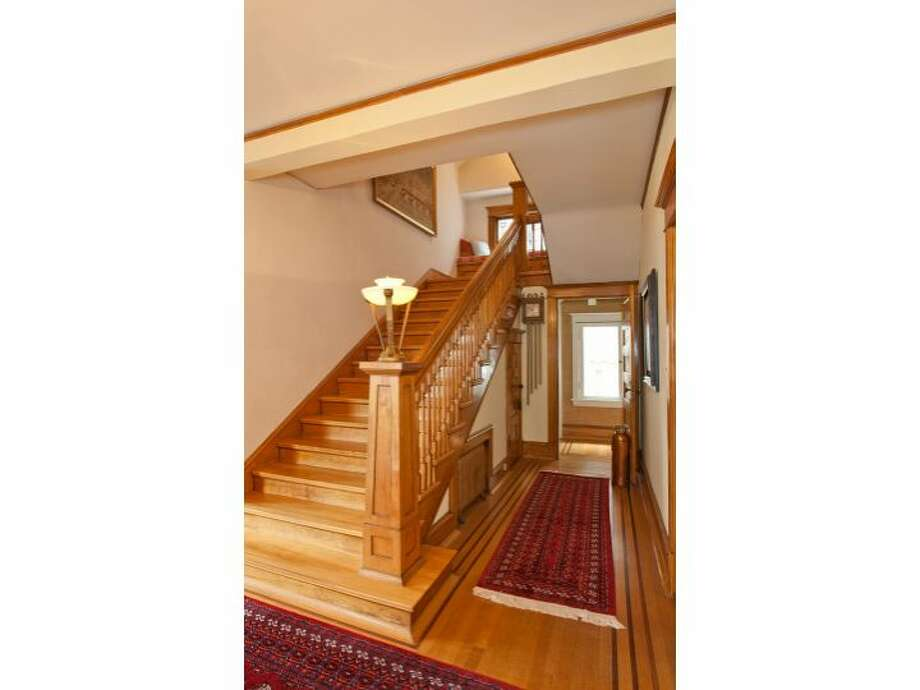 Staircase of 120 Prospect St., in Queen Anne. The 5,890-square-foot Georgian Colonial, built in 1904, has six bedrooms, four  bathrooms, a big foyer, birch millwork, leaded glass, a den, a sun porch, a White House-like balcony, a roof deck, a carriage house, a greenhouse, a trout pond with a waterfall, and views of downtown Seattle, Mount Rainier, Elliott Bay and Puget Sound on a 10,200-square-foot lot. It's listed for $1.695 million. Photo: Courtesy Mark Dagg, Windermere Real Estate